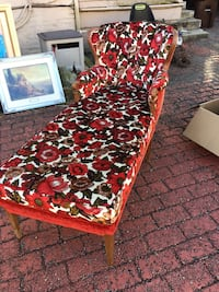 Brown wood-framed red and white floral cushion chaise lounge