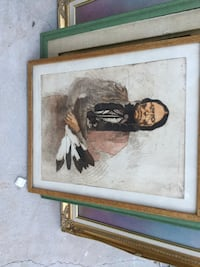 native american man in black and gray long-sleeved shirt painting with brown frame