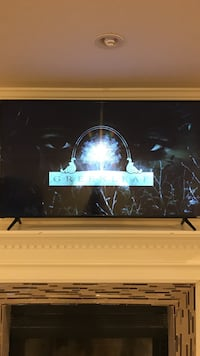 Black flat screen tv with black remote control