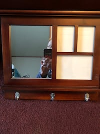 brown wooden mirror/ holds pictures and has hooks as well .  Downingtown, 19335