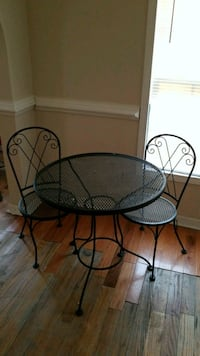 round black metal table with two chairs