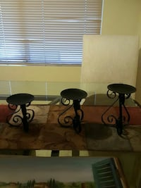 three black metal candle stands