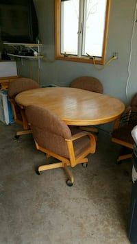 round brown wooden pedestal table with two chairs