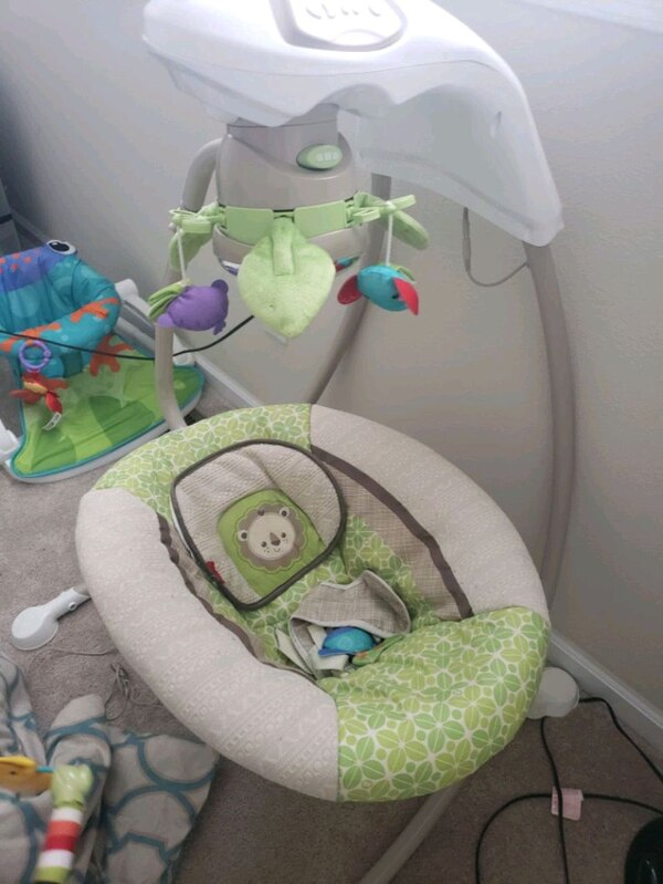 baby's green and white cradle and swing
