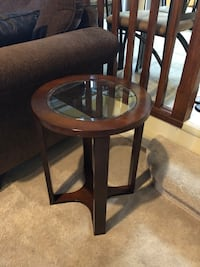 2  matching round wood and glass accent tables