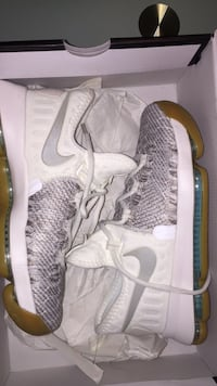 pair of gray Nike running shoes with box