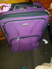 purple and black luggage bag