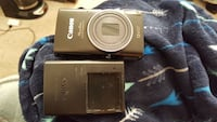 black Canon point-and-shoot camera with battery charger