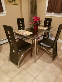 rectangular glass table with four black chairs