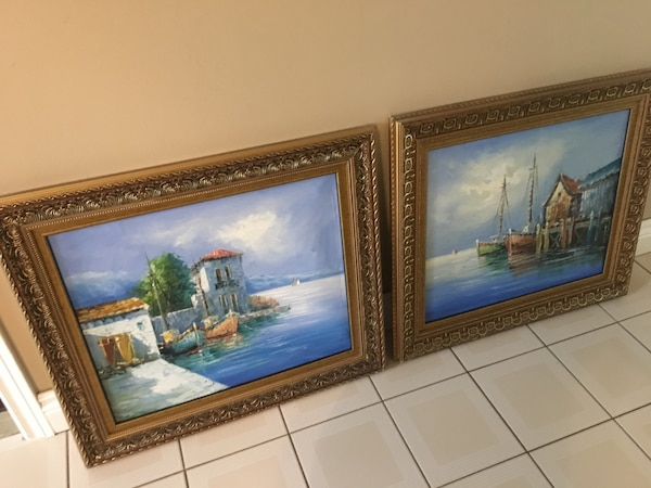 two brown wooden framed painting of house