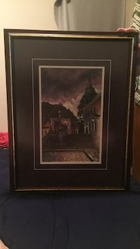 rectangular black wooden framed painting of brown and black rock building