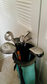 assorted stainless steel golf clubs in teal and bl