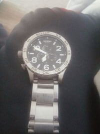 round black chronograph watch with silver link bra