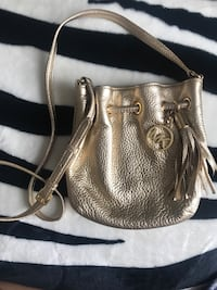 Gold color leather michael kors drawstring bag.