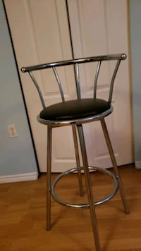 Three piece black and silver colored bar stools