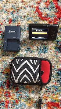 Black canon point-and-shoot camera with battery charger and pouch