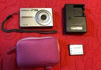 gray Olympus point-and-shoot camera with charger and pouch