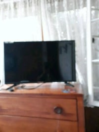 black flat screen TV; brown wooden TV stand Dundalk, 21222