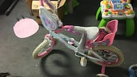 toddler's white and pink bicycle with training wheels