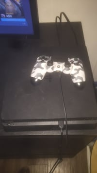 black Sony PS4 game console with controller Dollard-des-Ormeaux, H9B 2L4