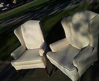 two white leather wingback armchairs