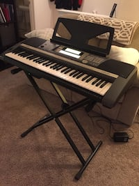 black and gray electronic keyboard with x-shape stand, carrying case and power cord
