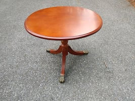 round brown wooden pedestal table with metal claw