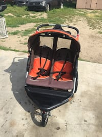 baby's orange and black twin jogging stroller