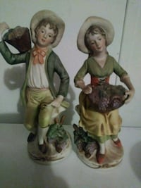 man and woman holding fruits ceramic figurines