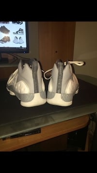 pair of gray-and-white Air Jordan 13 shoes