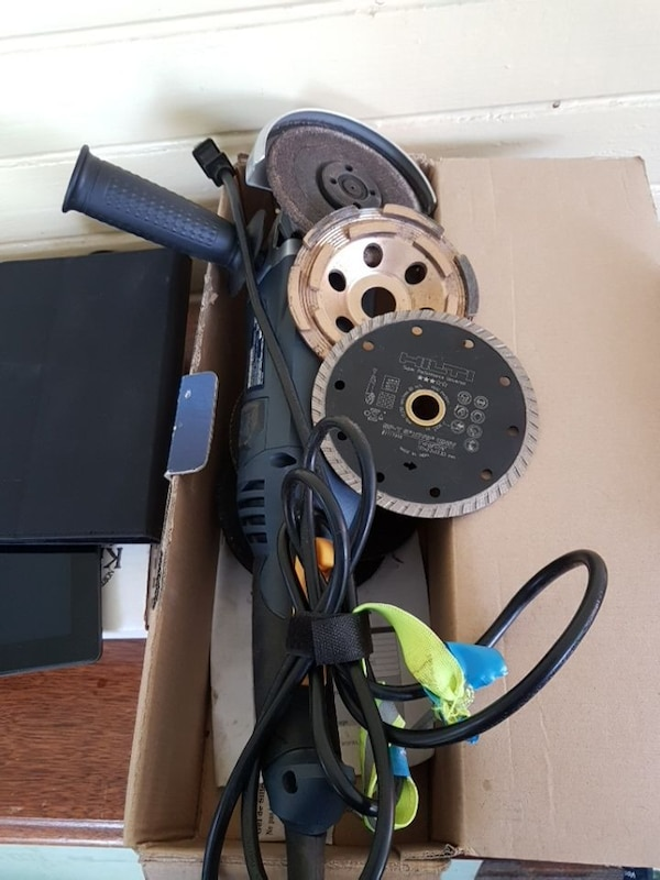 black and blue angle grinder with blades in box