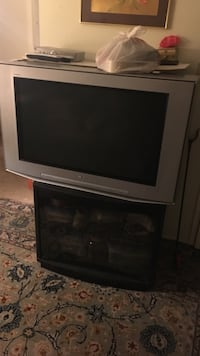 gray CRT television with TV stand