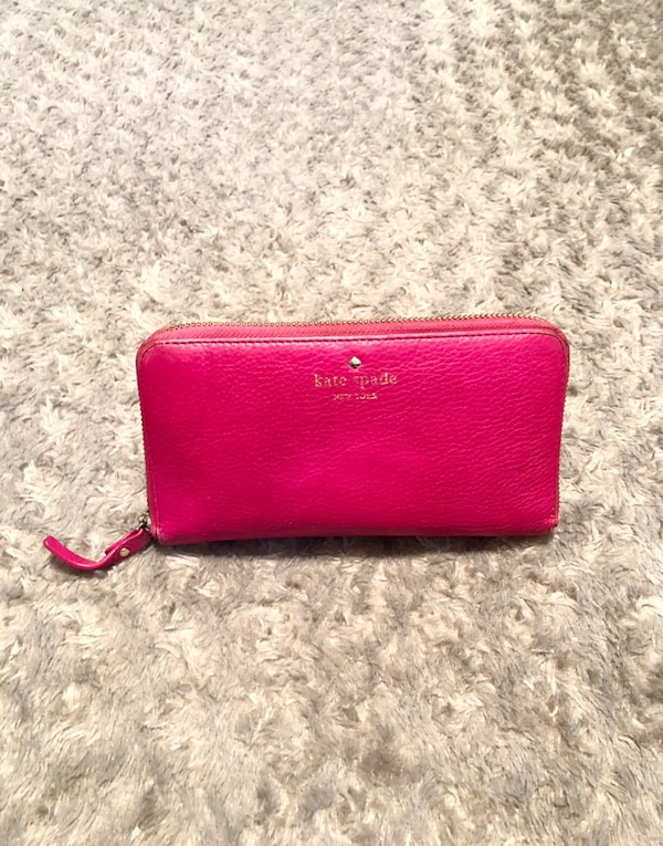 """Kate Spade wallet paid $178 good condition. The wraparound zip opens to a lined interior with a dividing zip pocket, checkbook compartment, 2 bill slots, and 12 card slots. Exterior back pocket. Measurements 7 ¾""""W x 4""""H x 1""""D. Has minor imperfections in o cea2302f-8b2e-4f01-b6b9-ca1a58a1b26e"""
