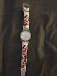 round silver analog watch with pink strap