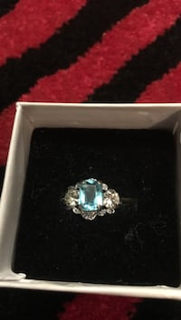 Rectangular silver-colored with teal gemstone ring, and white box Toronto