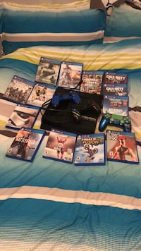 black Sony PS4 console with controller and game cases Grande Prairie, T8X 0C8