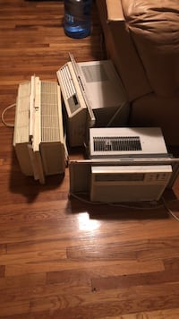 three white window-type air conditioners