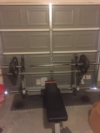 Black and gray bench press + Olympic bar and weights