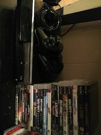 black Sony PS3 game console with controller andgam