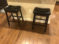 two black leather padded stools