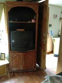 brown wooden TV hutch with black CRT TV