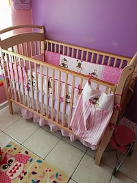 baby's brown wooden crib with white and pink crib bumper set