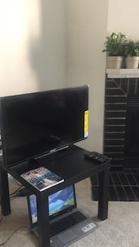 Black flat screen tv with black wooden tv stand Richmond, V6X 3H7