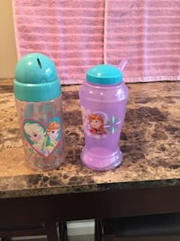 two green and pink plastic feeding bottles