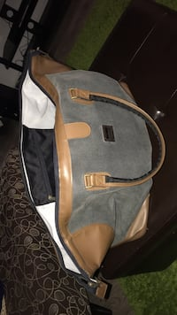Gray-brown leather duffle bag by michiko london brand ! Very sturdy .Rarely used . Doesn't come with straps . Travel handbag . Montréal, H4B