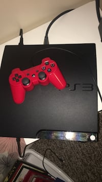 Black sony ps3 slim console with red controller