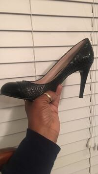 A pair of black snake skin pumps size 7.5