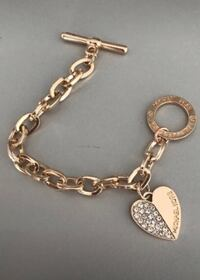 gold-colored chain link bracelet with toggle lock and heart charm