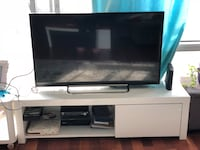 black flat screen TV with black wooden TV stand Montréal, H3J 2Z7