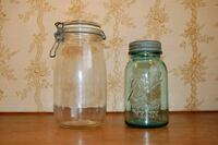 Two vintage glass mason jars, clear and blue
